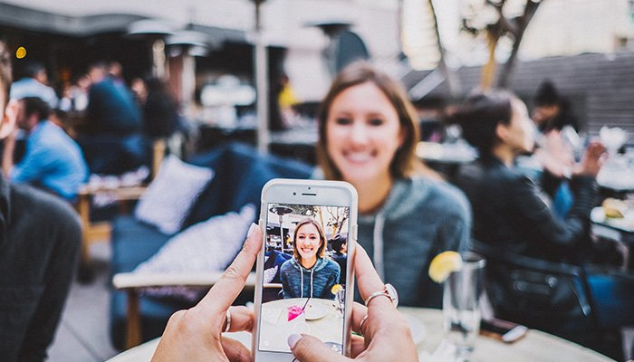 Person holding cell phone taking a photograph of smiling girl at restaurant table