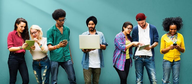 Young international students stand in a line with phones and laptops