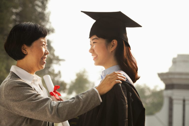 Young asian woman in graduation gown holding diploma with smiling mother