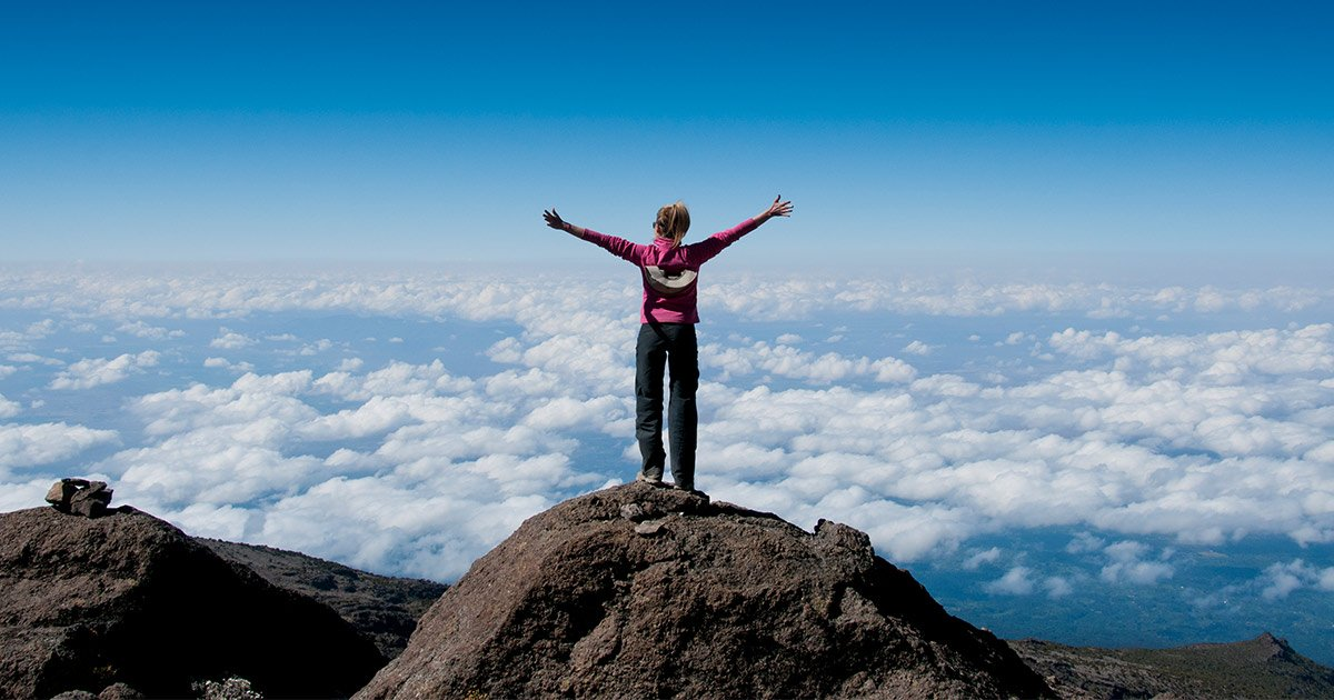 Woman standing at the summit of Kilimanjaro
