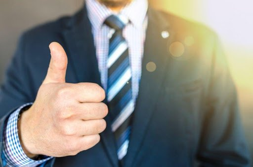 Man in suit and tie giving thumbs up