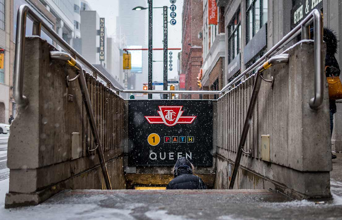 Person walking down steps into subway station in Toronto, Ontario