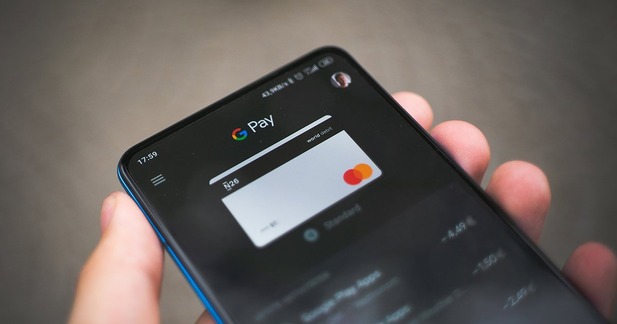 Hand holding a smart phone with the Google Pay app.