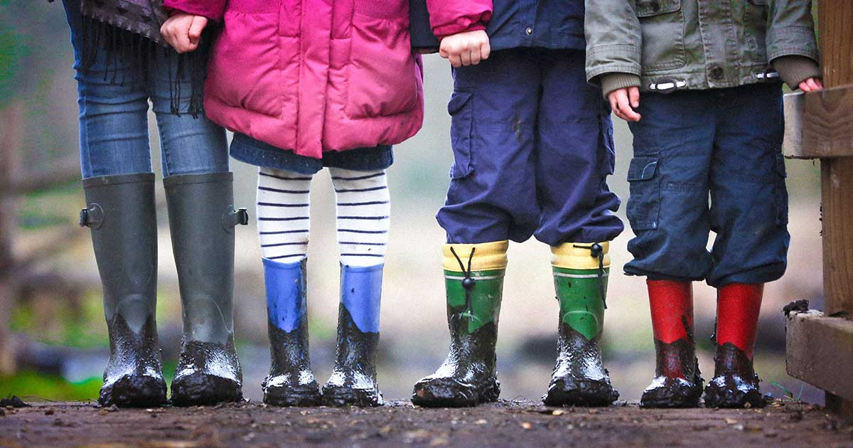 Four young kids lined up wearing dirty rubber boots.